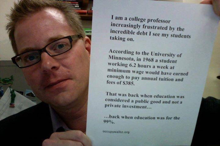Prof. David Davies holding a sign; caption below